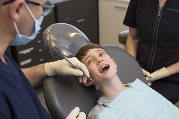 Family and children's dentist in Richmond, Melbourne applying fissure sealants to young child.